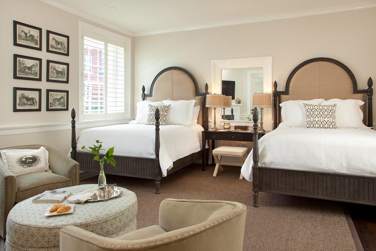 Two carved wooden and upholstered queen beds with white linens, black white and sage accents and six historic horse photos on the wall