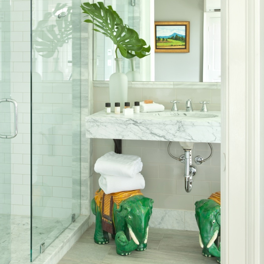 Two vintage elephant garden stools holding plush white towels under a marble vanity in beautiful bathroom