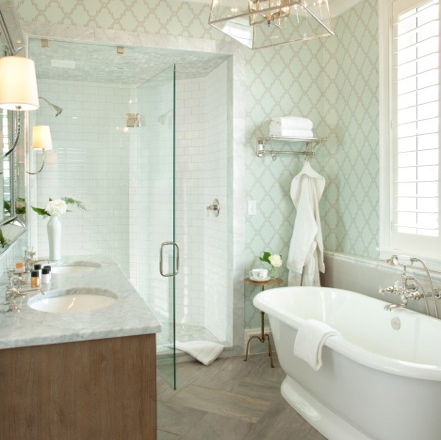 Natural light filled suite bathroom with freestanding soaking tub, marble and subway tile shower with glass door, marble topped fresh oak vanity and light green and gray trellis wallpaper