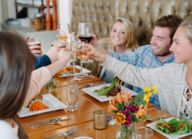 A group of people raising glasses to say cheers around a table at Haywood's