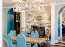 TAPS dining room with fireplace, blue velvet chairs, wooden farm table looking through arched doors into TAPS Lounge