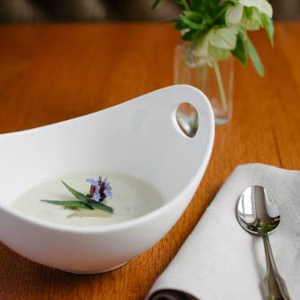 soup garnished with lavender blossom with a linen napkin and lenten rose arrangement on a table at Haywood's
