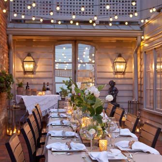 Private dinner party table setting with linen table cloth, barn wood runner and peony filled bud vases under bistro lights reflected in a mirrored French door in Haywood's Courtyard