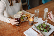 Couple enjoying a TAPS Burger and Simple Salad at table in TAPS