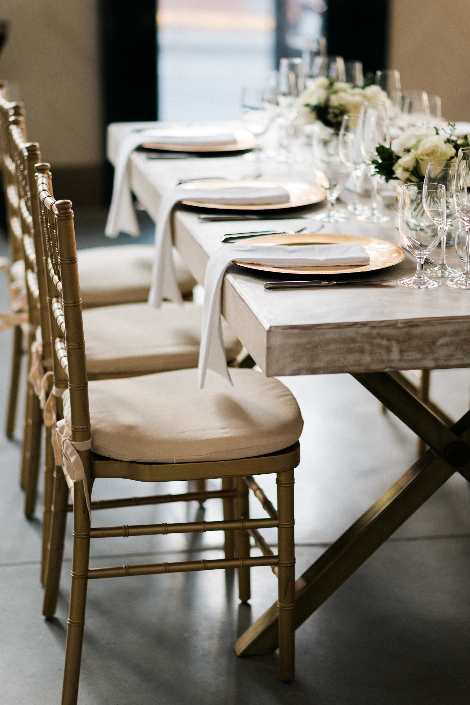 White washed wooden table set for a rehearsal dinner in The Patton Room