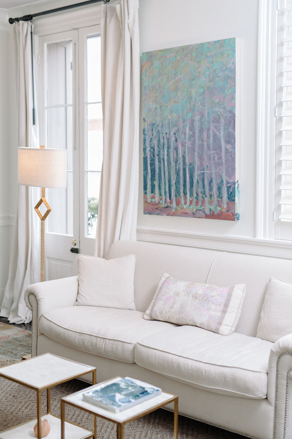 White couch under calming painting in sitting area of Room 2