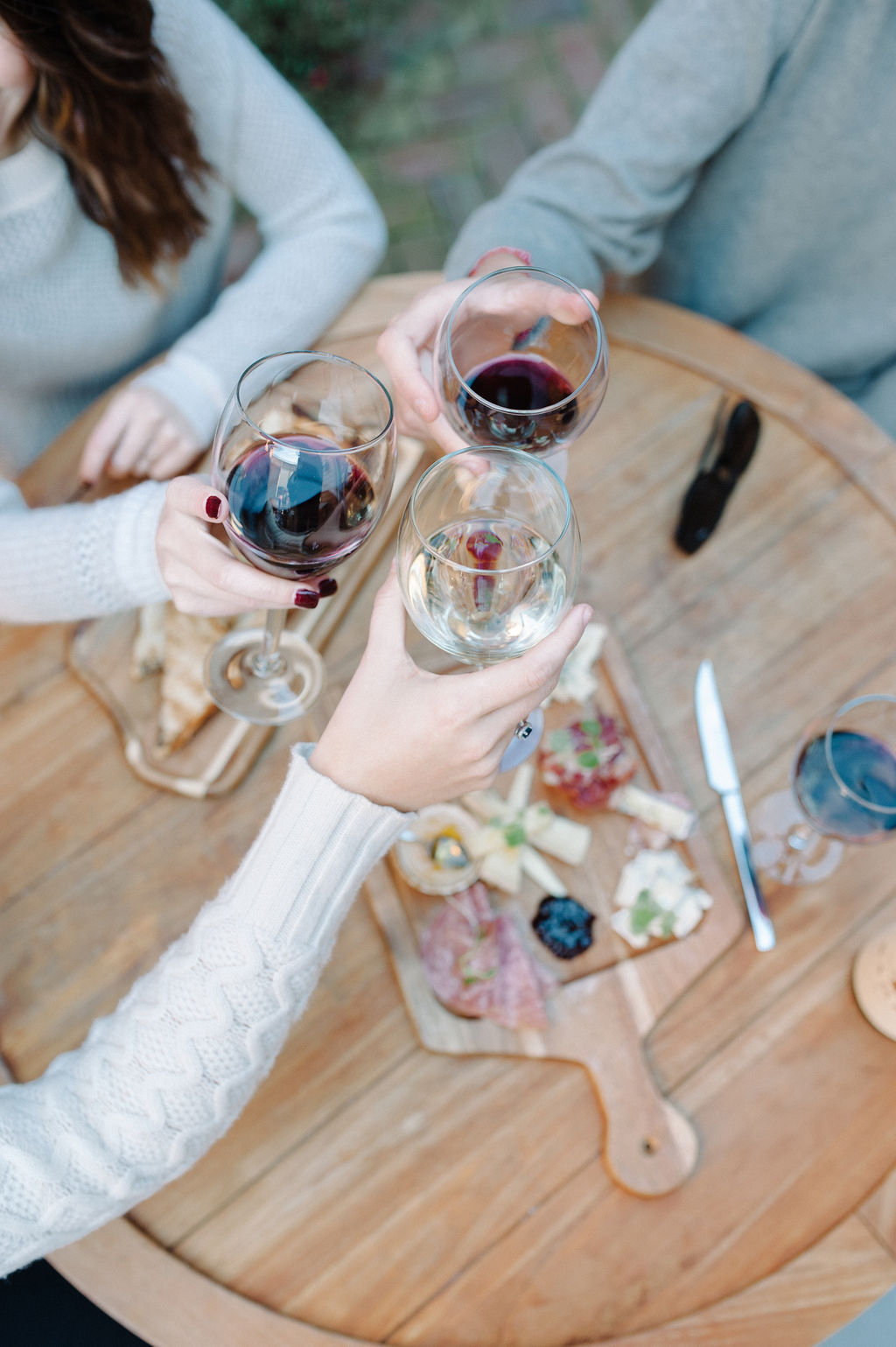 Three friends raising glasses of wine over a charcuterie board