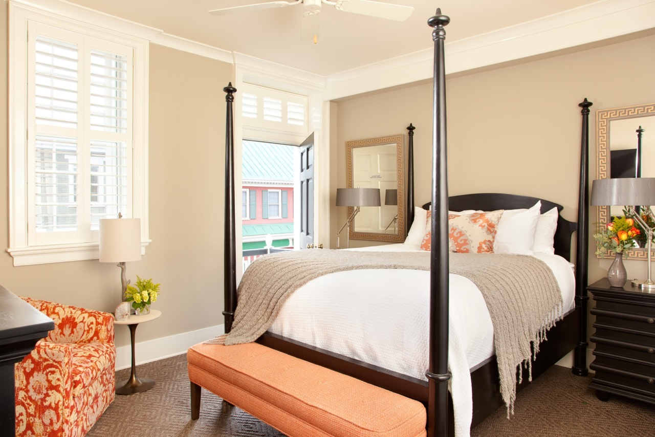 Tall four post bed with coral bench in Room 9 and view of Main Street