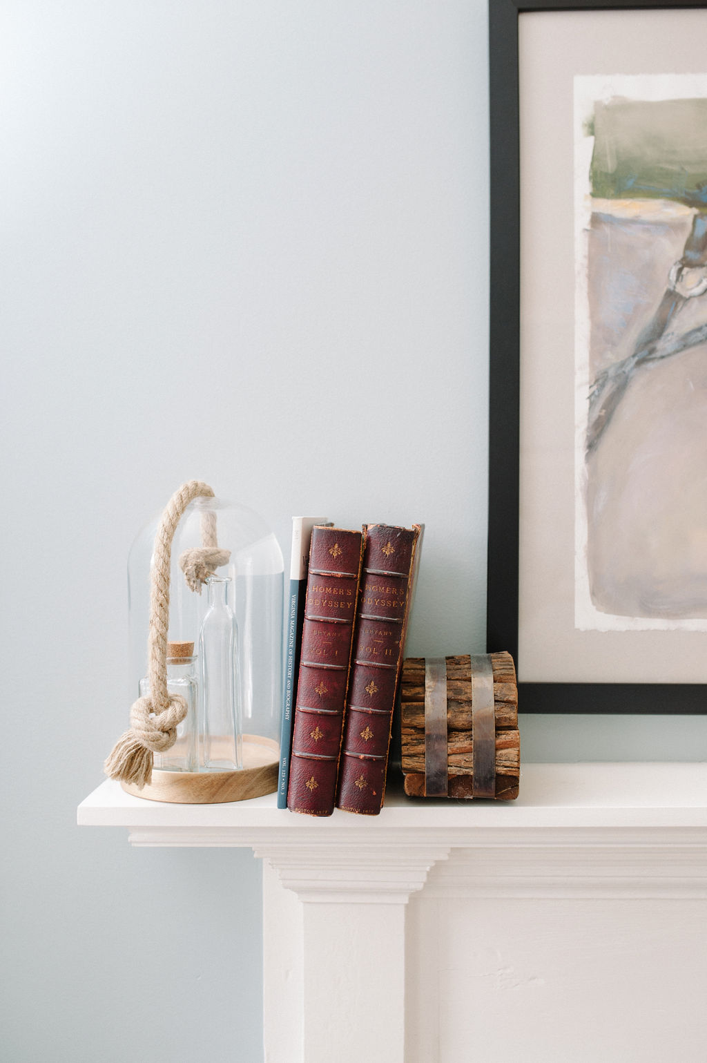 Detail of sculpture and books on white traditional mantlepiece in Room 7
