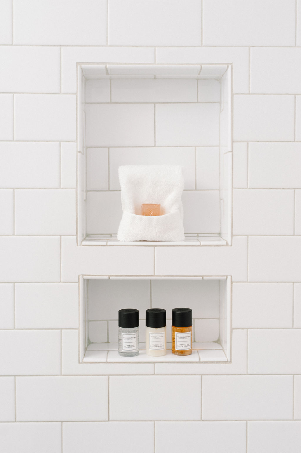 Calming white tile with amenities in bathroom of Room 8