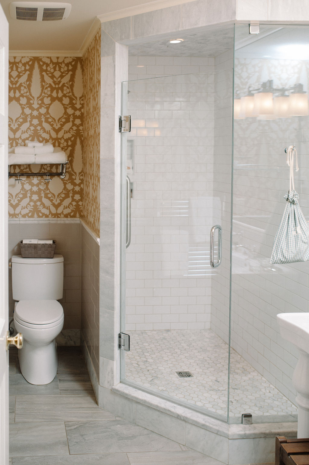 Walk in shower and patterned yellow and white wallpaper in bathroom of Room 9