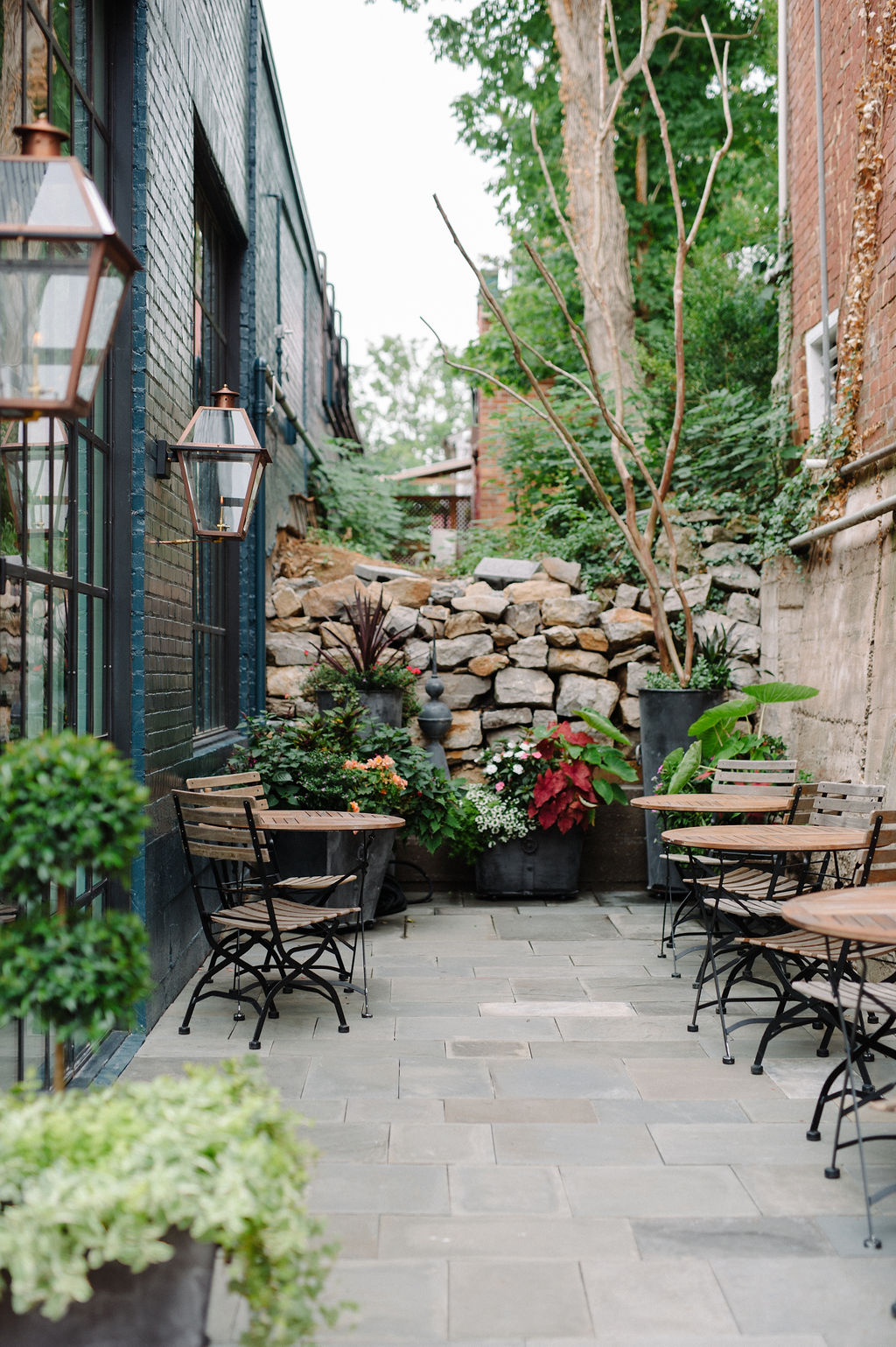 An outdoor patio space with wood and iron tables and chairs that is attached to The Patton Room